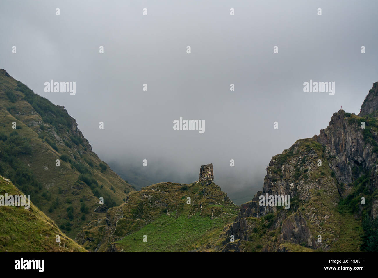 A lone stone tower shelter in ruins stands on top of a rocky hill surrounded by bigger rocky mountains and low cloudy mist. - Stock Image
