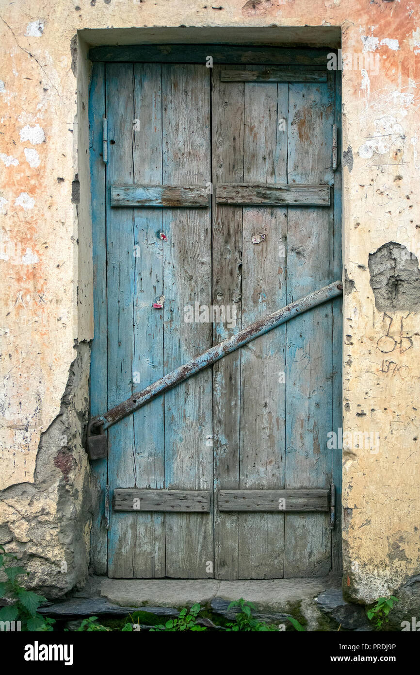 An Old Rustic Slatted Wooden Door With Faded Blue Paint Stands In A Plaster  Stone Walled Door Way.