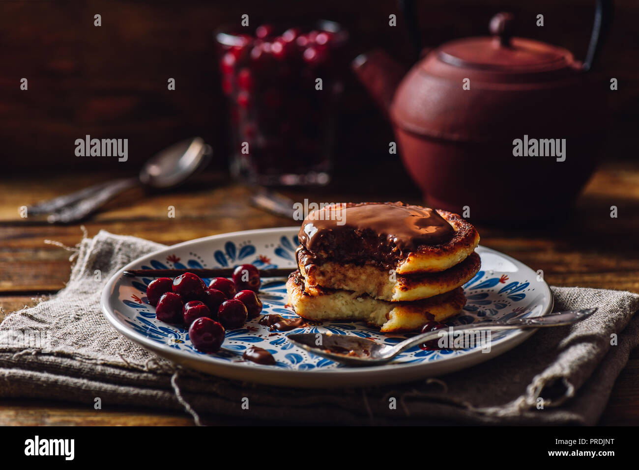 Quark Pancakes with Chocolate Topping, Frozen Cherry and Vanilla Pod. Tea Pot with Spoons and Glass of Berries on Background. - Stock Image