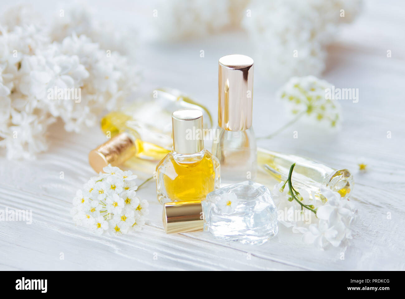 Bottles Of Perfume With White Flowers On Wooden Background Stock
