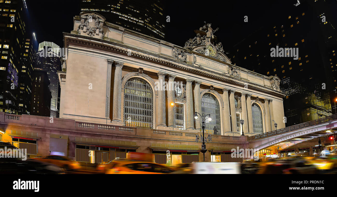 Grand Central Station lit up at night, with blurs of passing cars showing fast paced motion concept - Stock Image