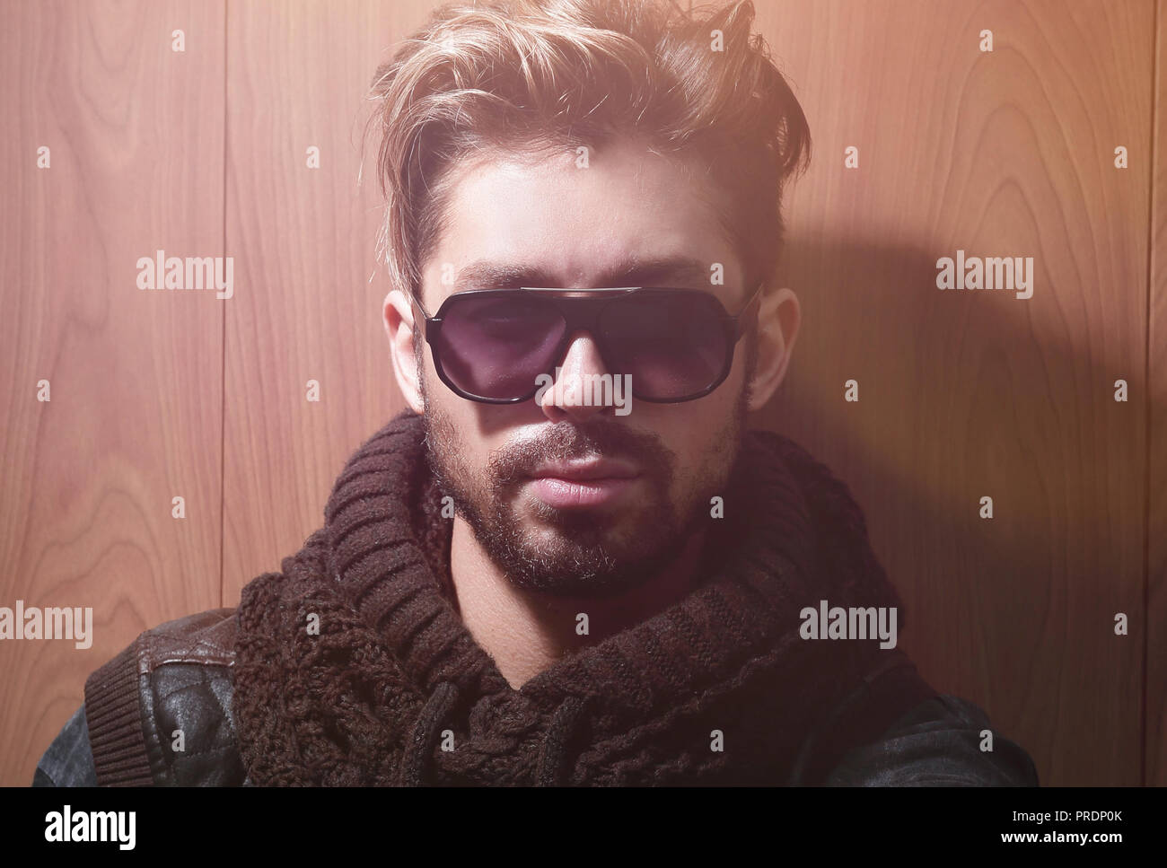 Portrait of a handsome mature man in sunglasses over wooden wall background. Men's beauty, fashion. - Stock Image