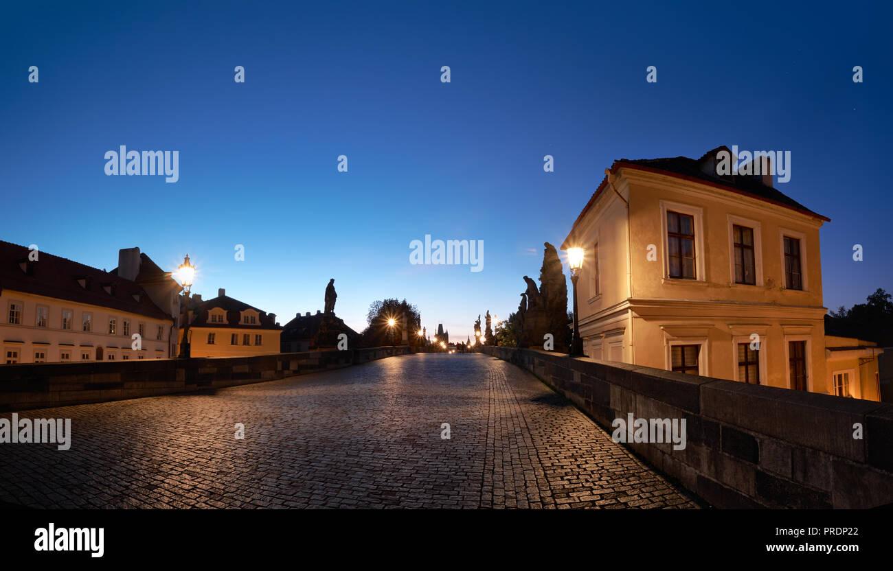 Prague at night, illuminated historical houses and Charles Bridge after rain with wet cobblestones - Stock Image