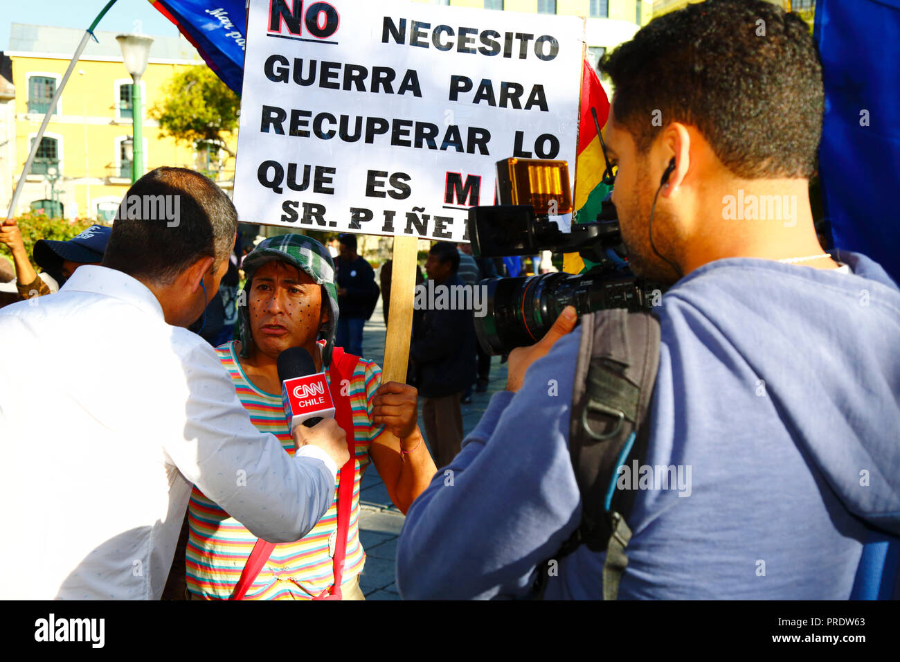 La Paz, Bolivia, 1st October 2018. A man dressed up as the famous Mexican TV character El Chavo from the sitcom El Chavo del Ocho speaks to a CNN Chile reporter before the reading of the ruling for the case 'Obligation to Negotiate Access to the Pacific Ocean (Bolivia v. Chile)' at the International Court of Justice in The Hague. Bolivia presented the case to the ICJ in 2013; Bolivia lost its coastal Litoral province to Chile during the War of the Pacific in the 19th century and previous negotiations have made no progress from Bolivia's viewpoint. Credit: James Brunker/Alamy Live News - Stock Image