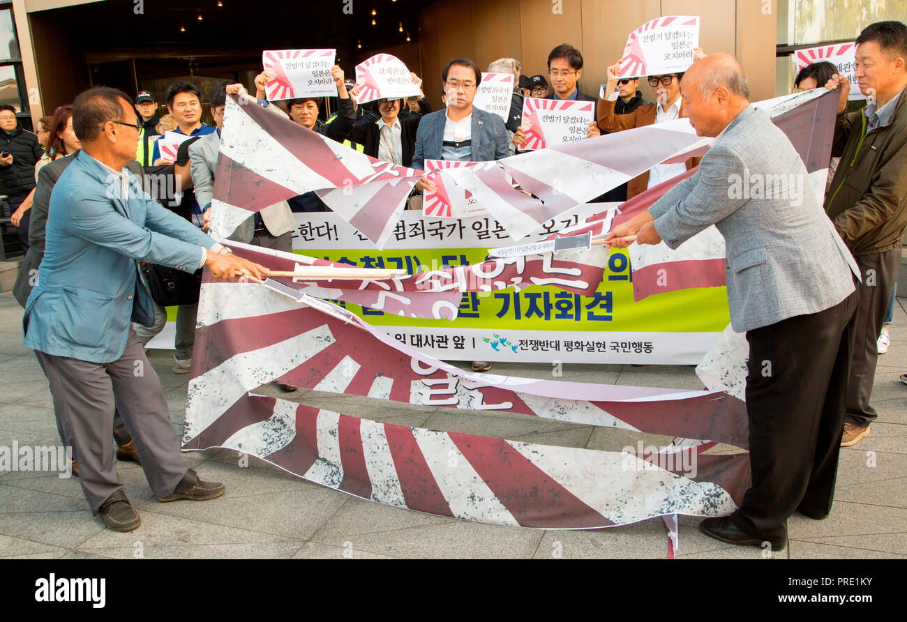 Protest against Japanese rising sun flag in South Korea, Oct 1, 2018 : South Korean activists from civic groups cut a mock Japanese rising sun flag during a press conference in front of the Japanese embassy in Seoul, South Korea. The protesters criticized Japan and its navy planning to display Japanese Rising Sun Flag, which protesters think as a symbol of wartime aggression, during the International Fleet Review to be held off the island of Jeju, South Korea from October 10-14. Navy ships from 15 countries including Japan, China and the U.S. will participate in the event. South Korean navy sa - Stock Image