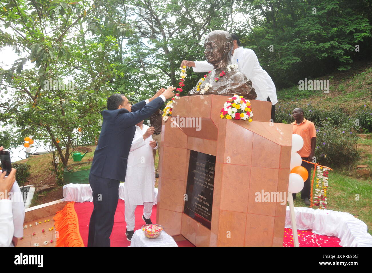 Jinja, Uganda. 2nd October, 2018: The High Commissioner of India in Uganda Ravi Shankar (left) garlanding Mahatma Gandhi's Statue with flowers during celebrations to mark Mahatma Gandhi's 149th Birthday and UN International Day of Non Violence at the Source of the Nile in Jinja. Members of the Indian Association Uganda, officials from Busoga Kingdom Tourism Ministry and Jinja residents joined other Indians all over the World in celebrating the 149th birthday of Mahatma Gandhi and the International Day of Non-Violence. In Uganda, they garlanded Mahatma Gandhi's Statue with flowers. Credit: Dona - Stock Image