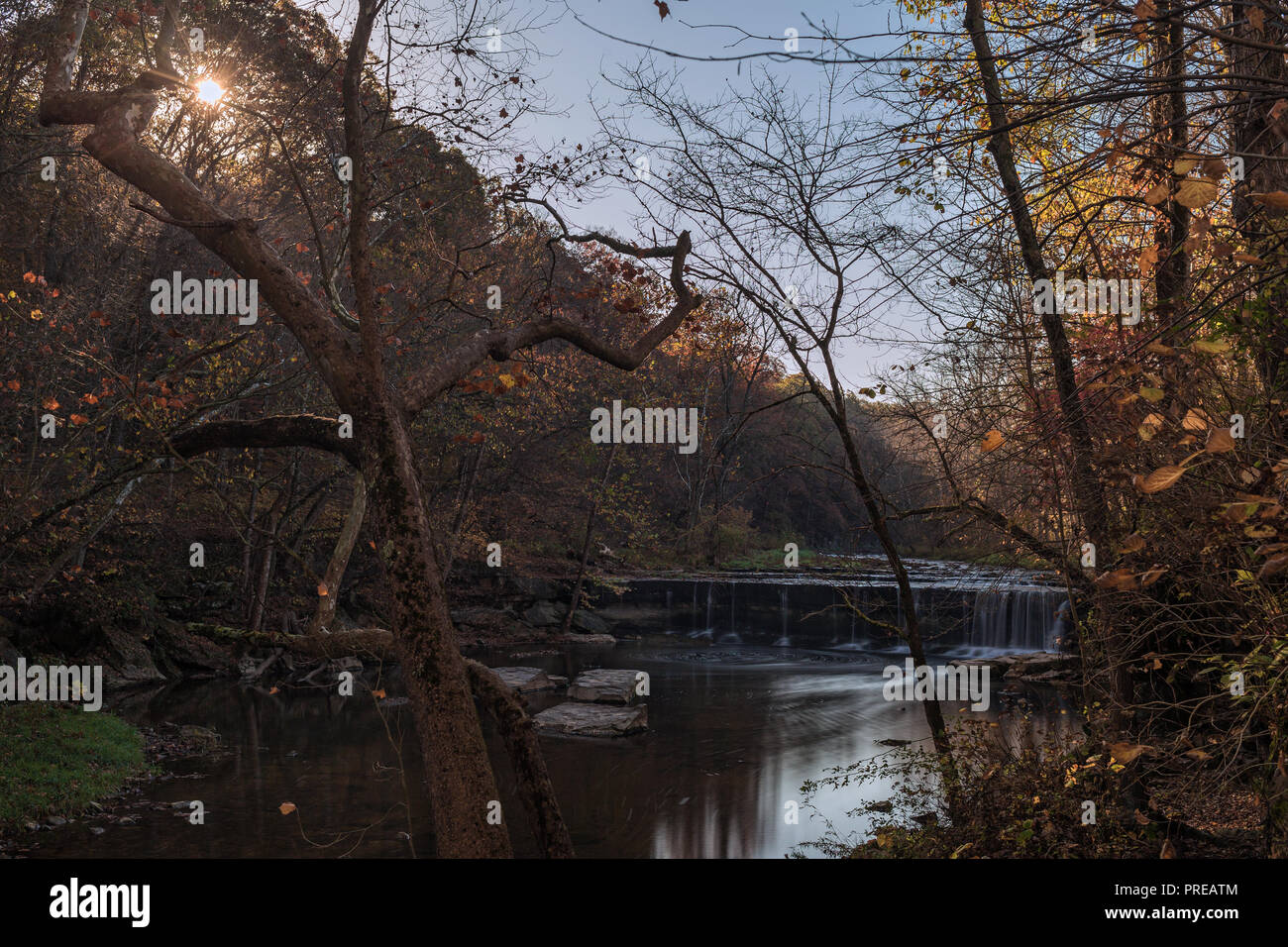 The sun peaks through a line of trees on Clifty Creek in Bartholomew County, IN.  Anderson Falls is in the background of this fall scene. - Stock Image