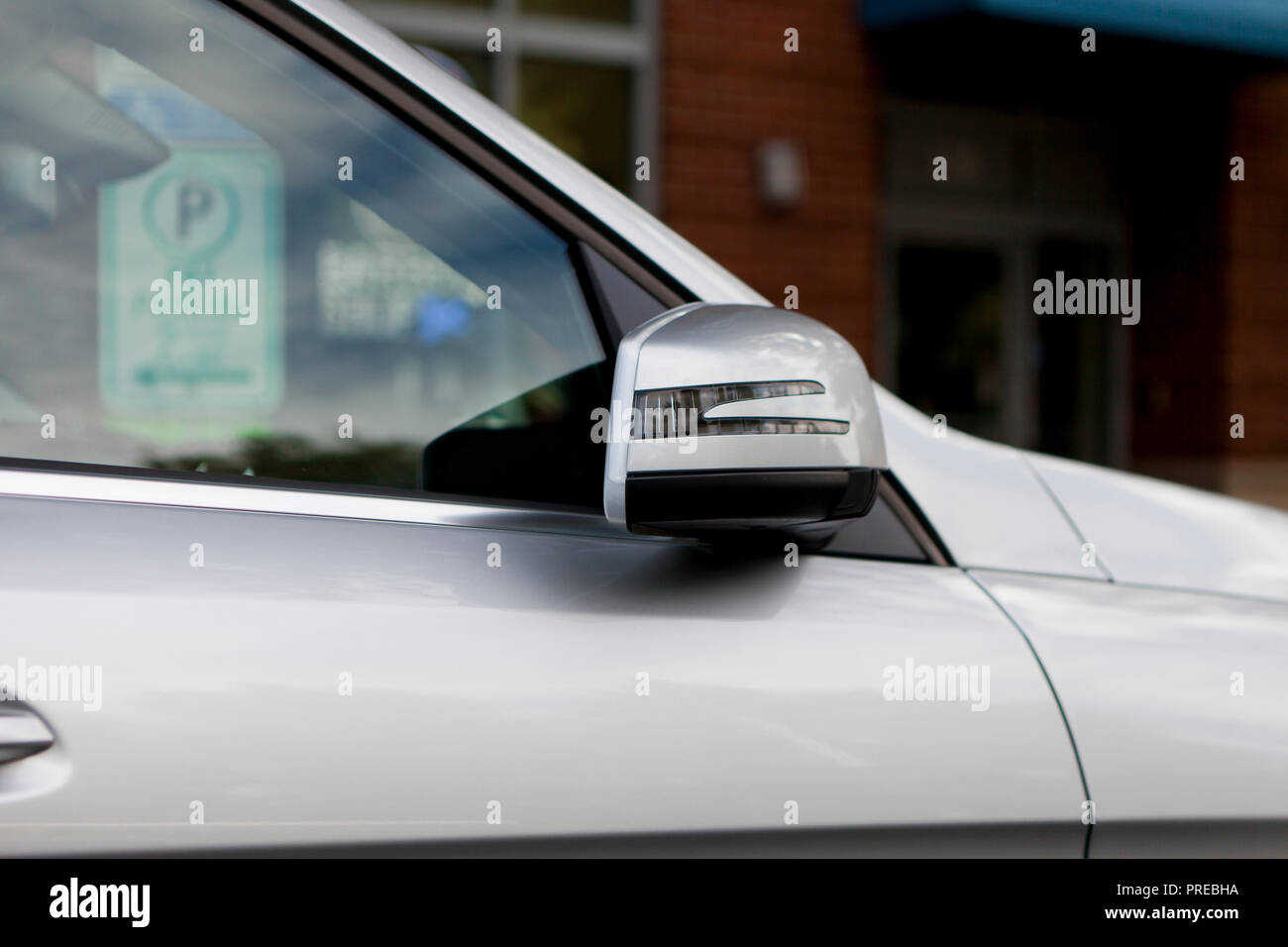 Folded side mirror of passenger car, parked on street (folding side mirror) - USA - Stock Image