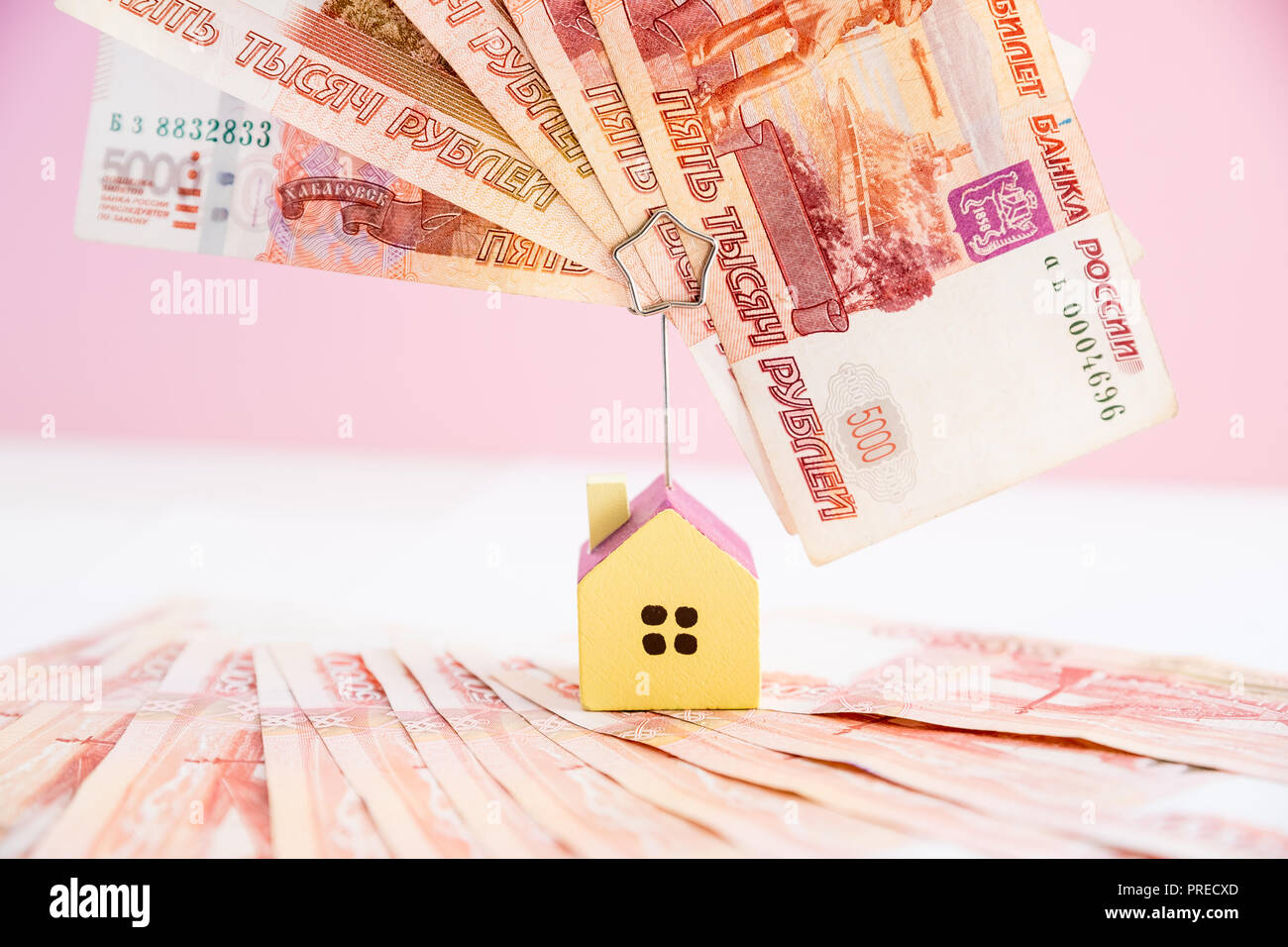 Model of the house standing on five thousand banknotes.Rental estate.Sale property template.Model of wooden house with money. House building, loan,real estate, cost of housing or buying a new home concept. - Stock Image