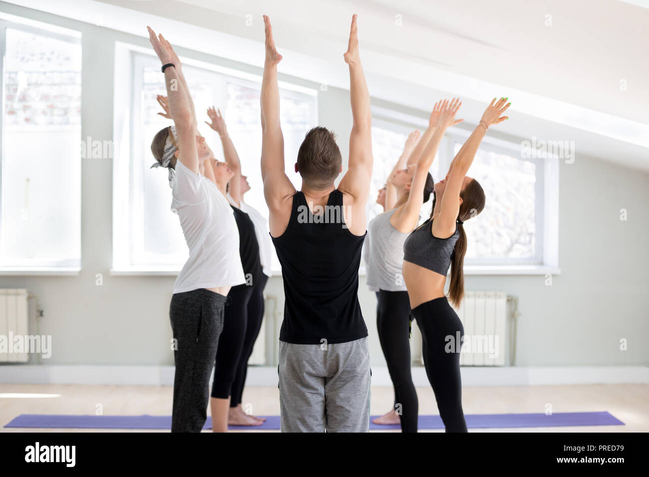 Group of young sporty people practicing yoga lesson, doing Tadasana exercise, mountain pose, working out, indoor full length, yogi students training i Stock Photo