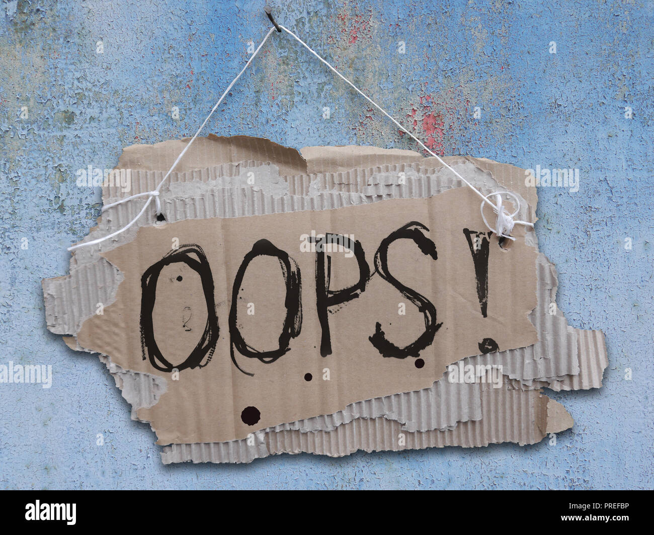 Cardboard sign on a cord with a words OOPS. Ripped, corrugated paper with white sign OOPS hanging on a nail on a cracked wall. - Stock Image