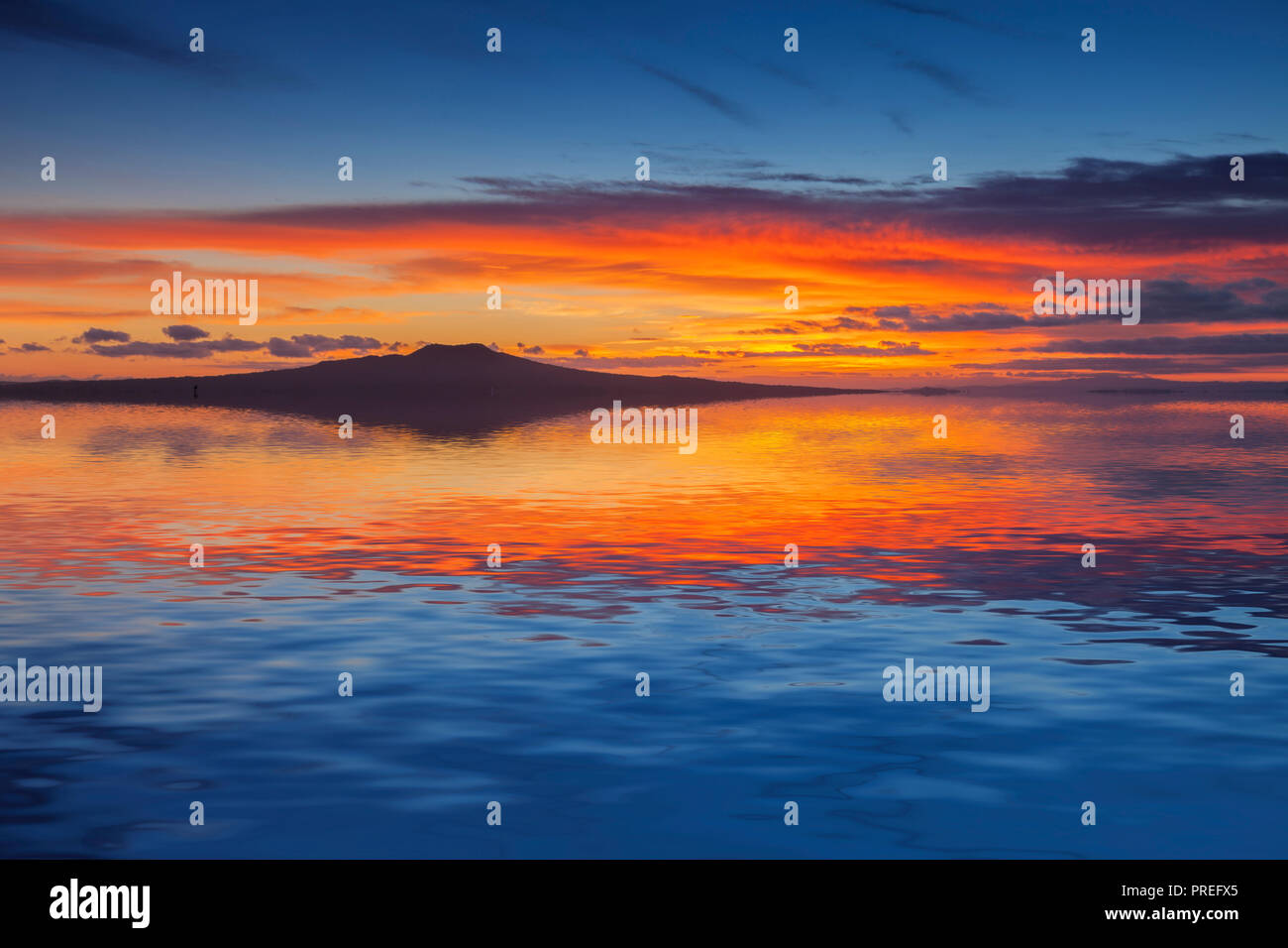 Rangitoto Island at sunrise, Auckland, New Zealand, reflected in the waters of the Hauraki Gulf. Stock Photo