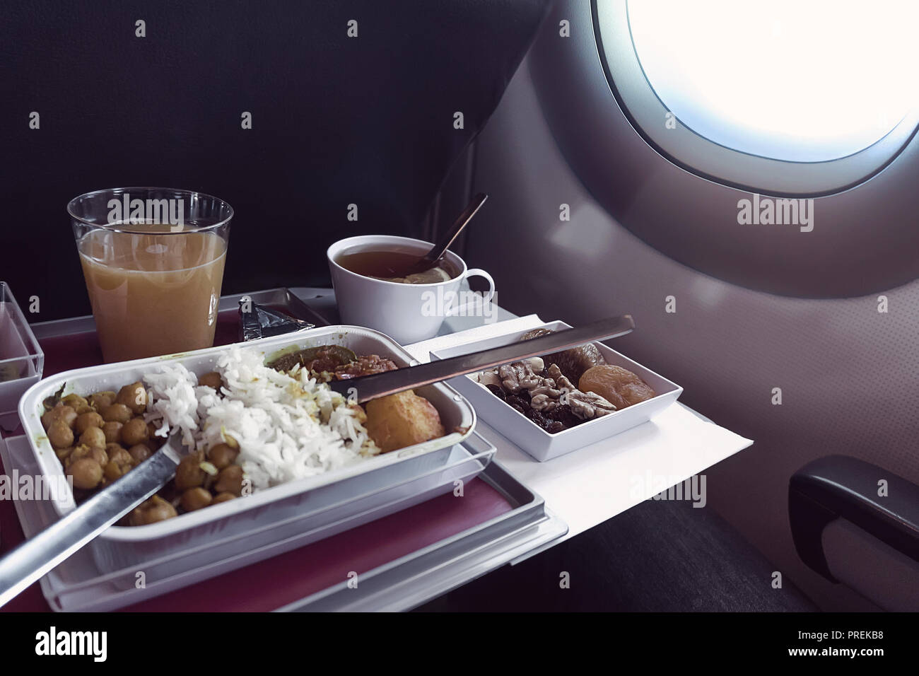 Set of inflight meal in a box, on the folding table in economy class. Feeding the passengers of Asian food on the plane in Kazakhstan. The journey tou - Stock Image