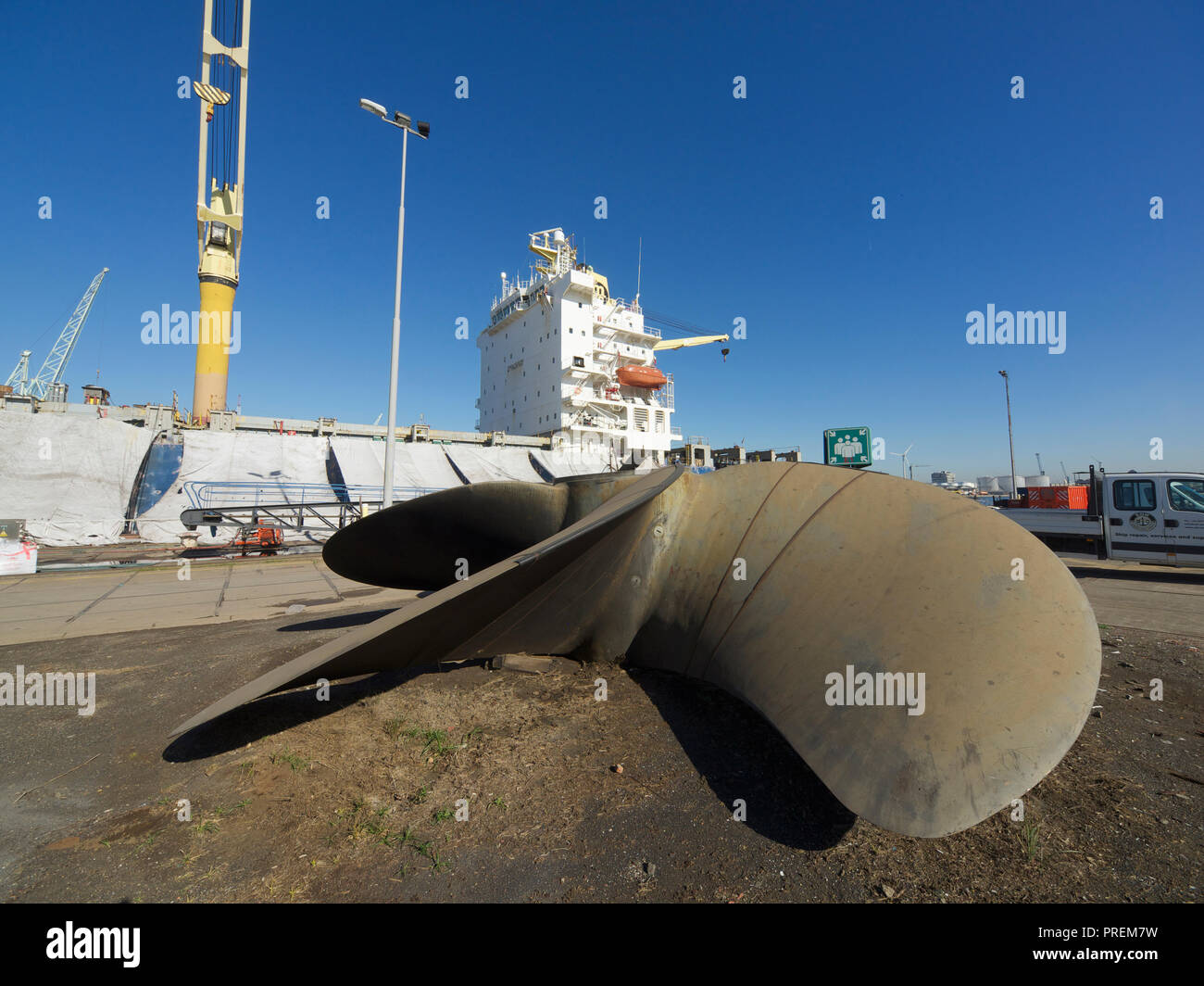 Cargo ship in dry dock for maintenance with large propeller in the foreground, port of Antwerp, Belgium - Stock Image