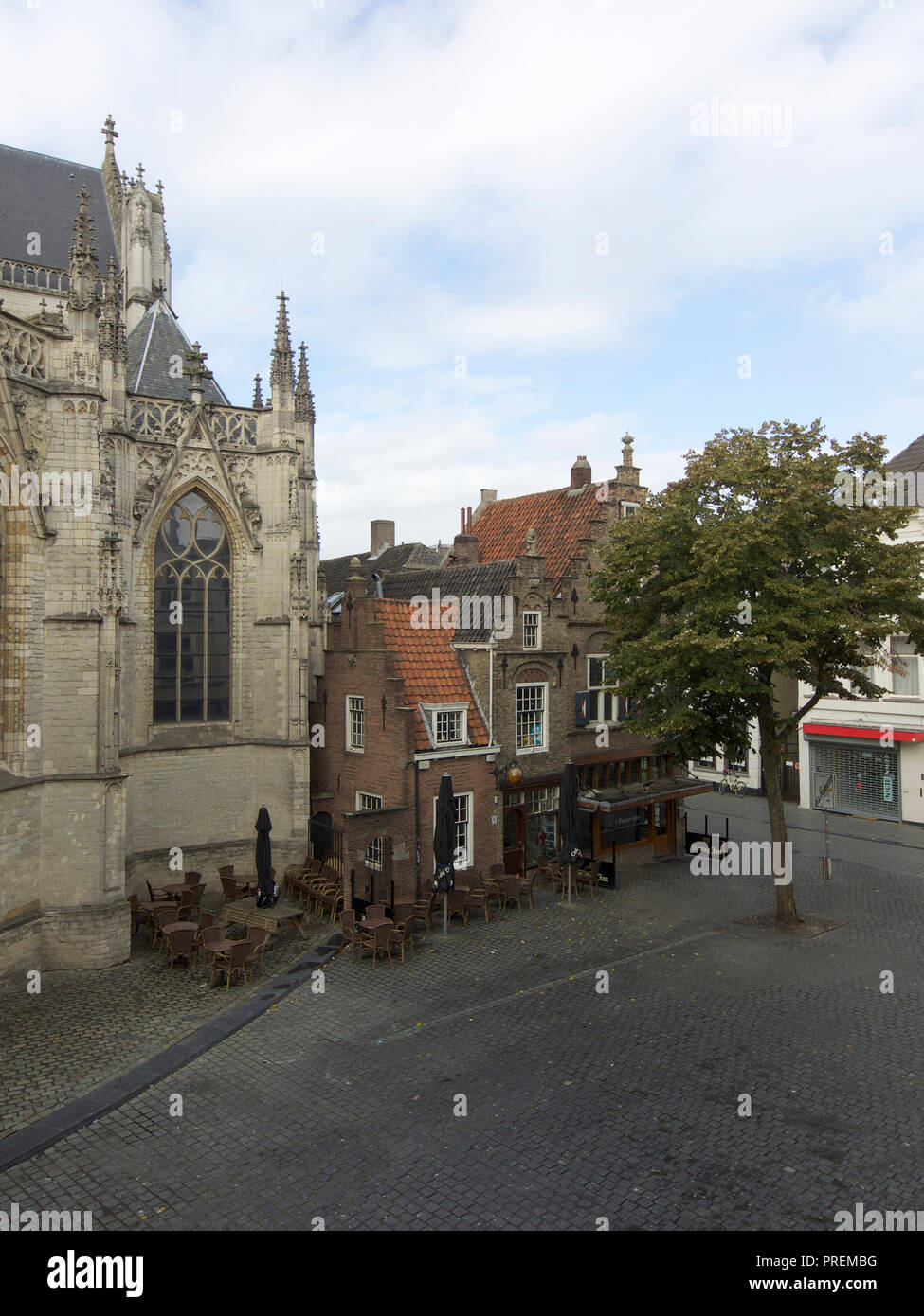 Small medieval buildings next to the grand chruch of Breda. - Stock Image