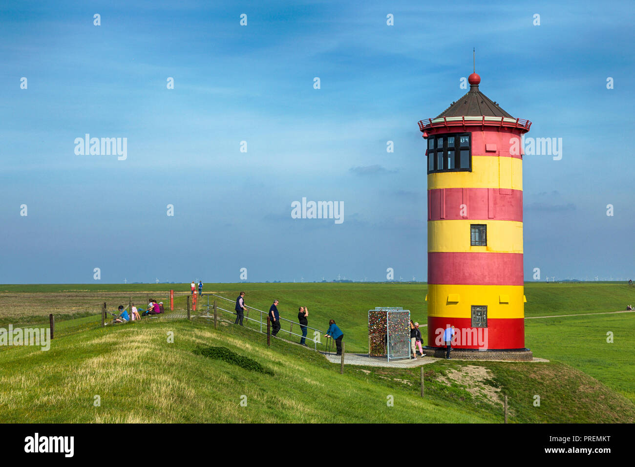 Pilsum lighthouse in East Frisia, tourists walking around, sitting on the dike and taking photographs - Stock Image