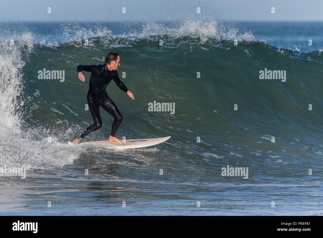 Surfer in black wetsuit finds smooth and glassy section of wave at Surfer's Knoll, Ventura, California on October 1, 2018. Stock Photo