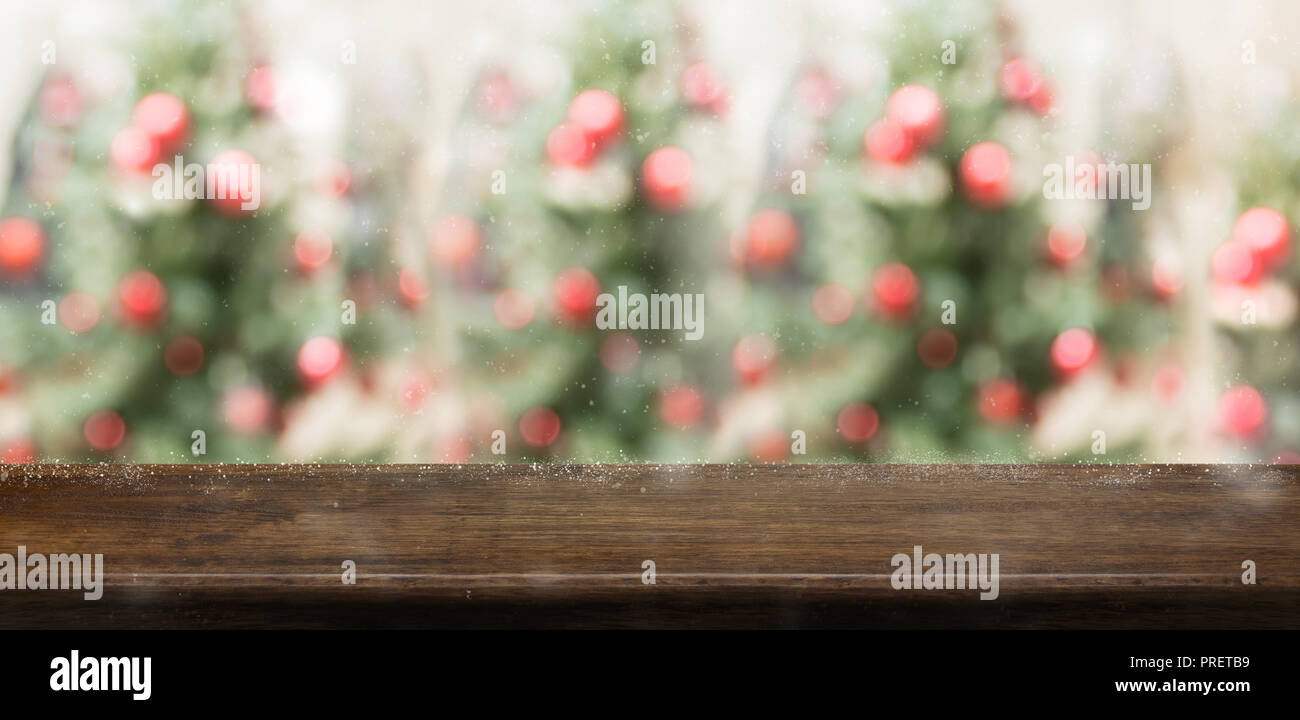 Empty rustic wood table top with abstract blur christmas tree red decor ball and snow fall background with bokeh light,winter Holiday backdrop,Mock up - Stock Image