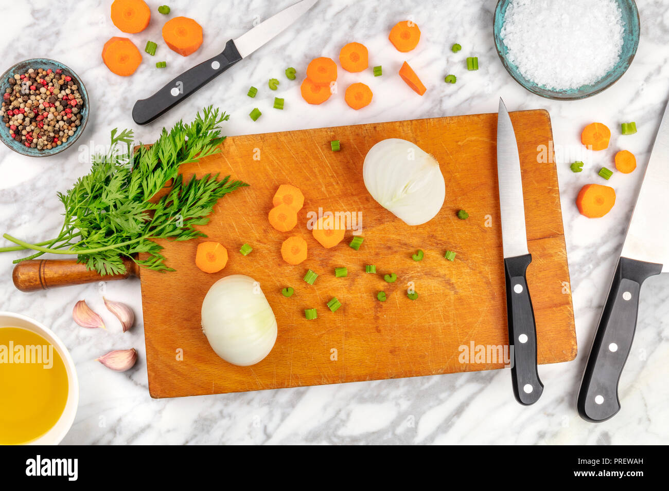 Prep time, or mise en place. An overhead photo of professional chef's knives, shot from above on a cutting board, with chopped vegetables and spices, on a marble cooking surface - Stock Image