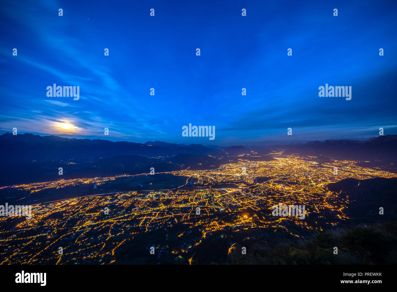 Aerial of Grenoble at night with moon rising over the mountains. - Stock Image