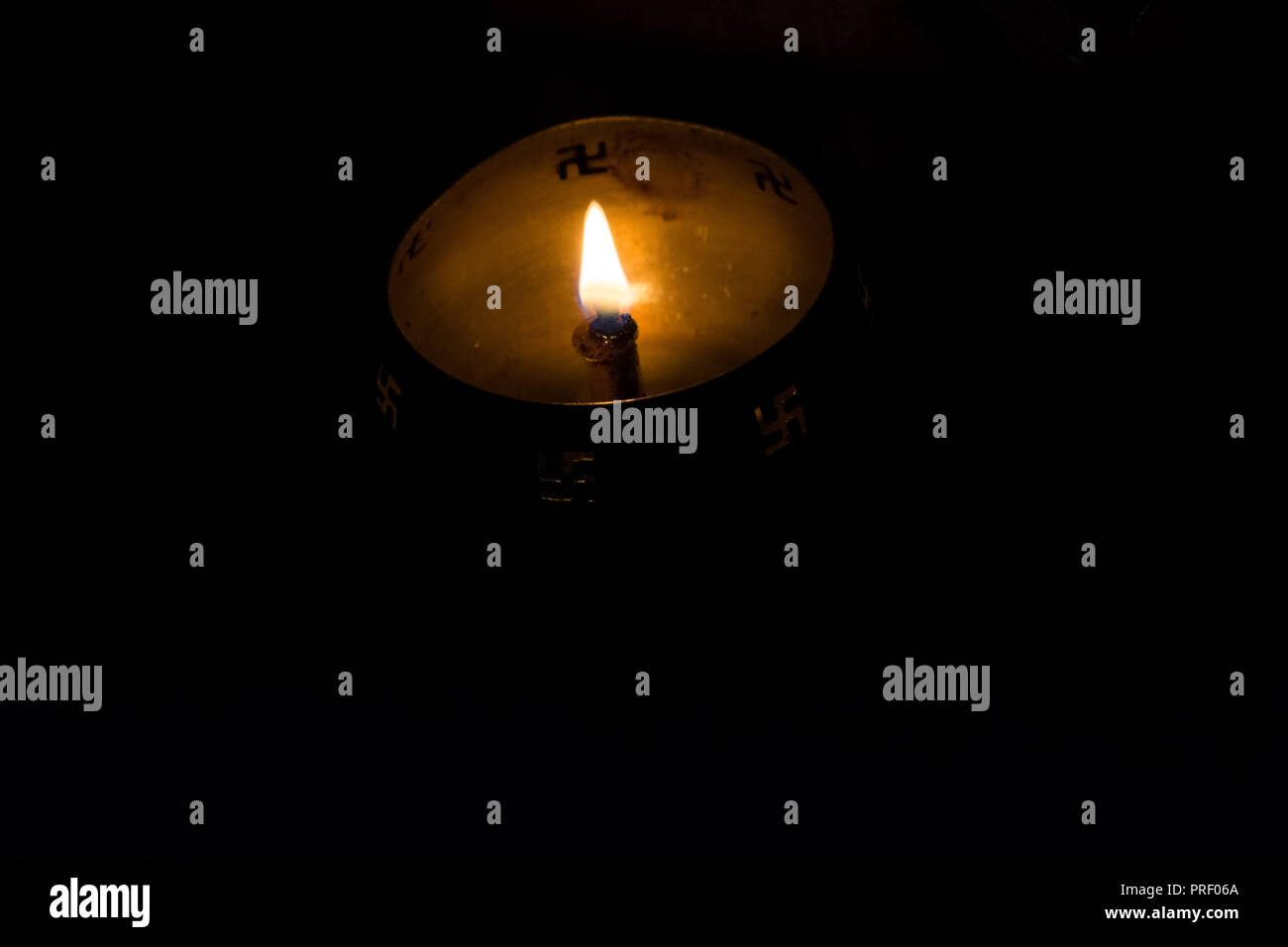Flame of oil lamp on dark background, a burning oil lamp in darkness, with copy space. concept of removing darkness with a flame, are common in india  - Stock Image