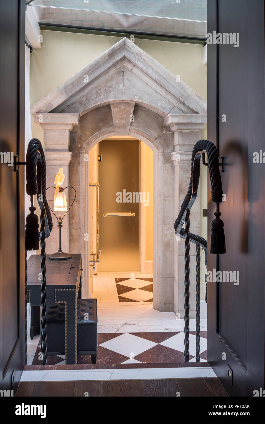 Stone pediment, originally a window surround, as entrance to shower - Stock Image