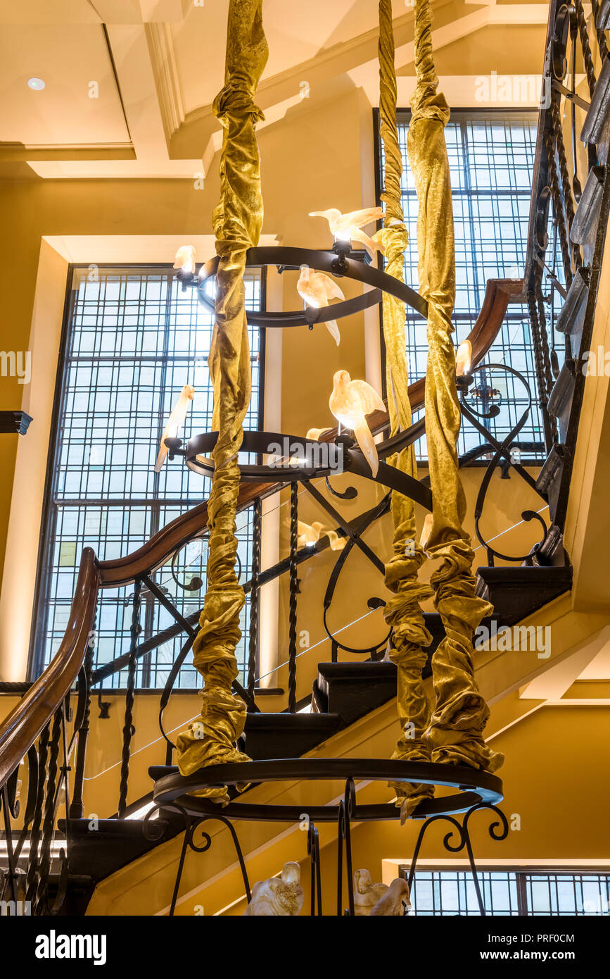 Original staircase running seven stories of building, with amber glass birds - Stock Image