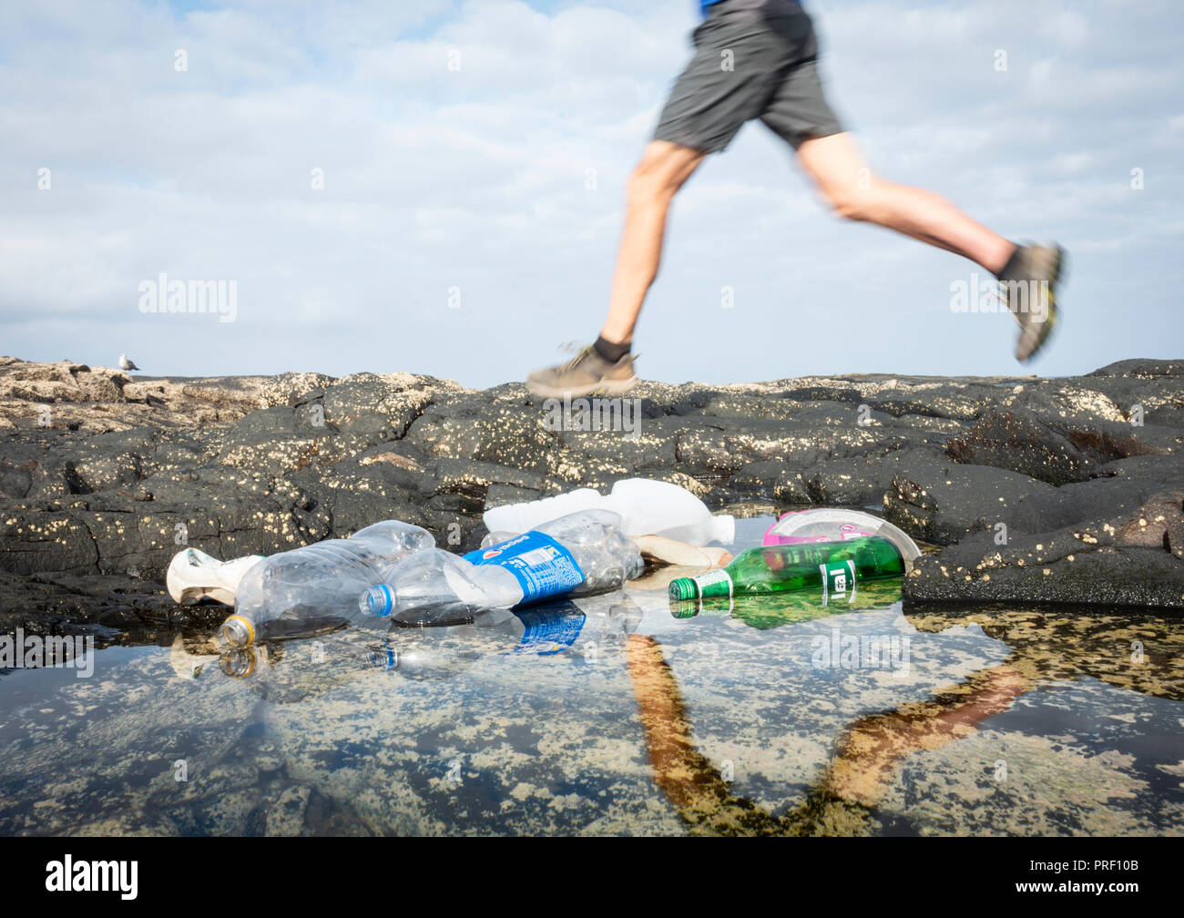 Low angle view of jogger running past plastic bottles in coastal beach rockpool, - Stock Image