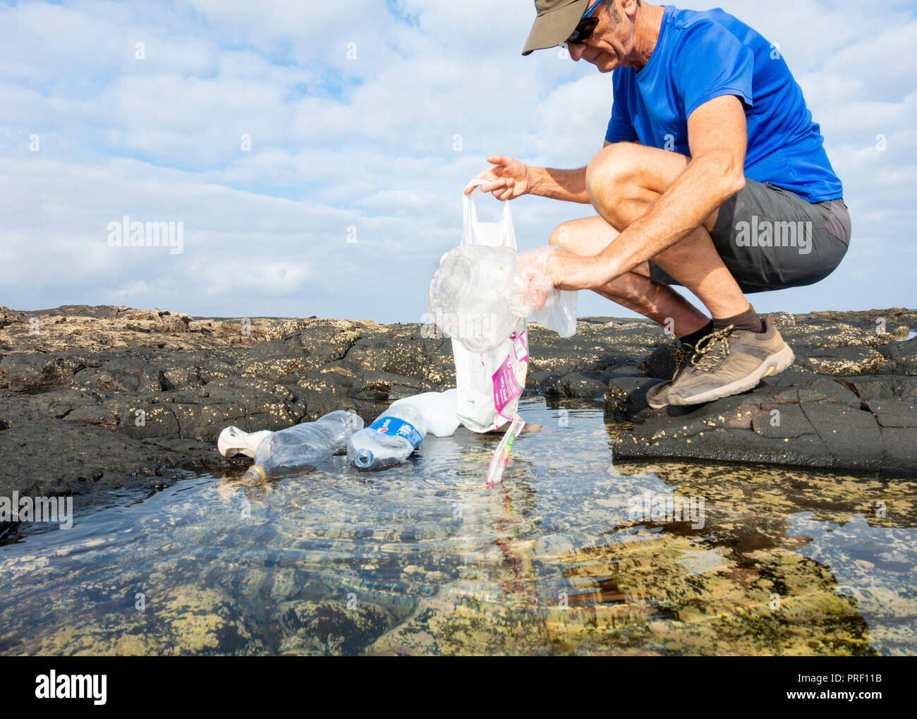 A Plogger/jogger collects plastic rubbish from beach rockpool during his morning run - Stock Image