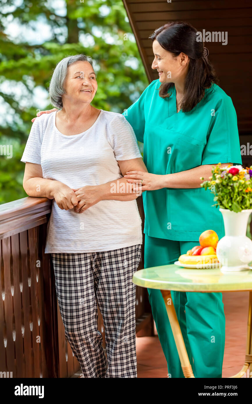 Senior woman with her home caregiver spending time together. Female nurse consoling senior woman at home. - Stock Image