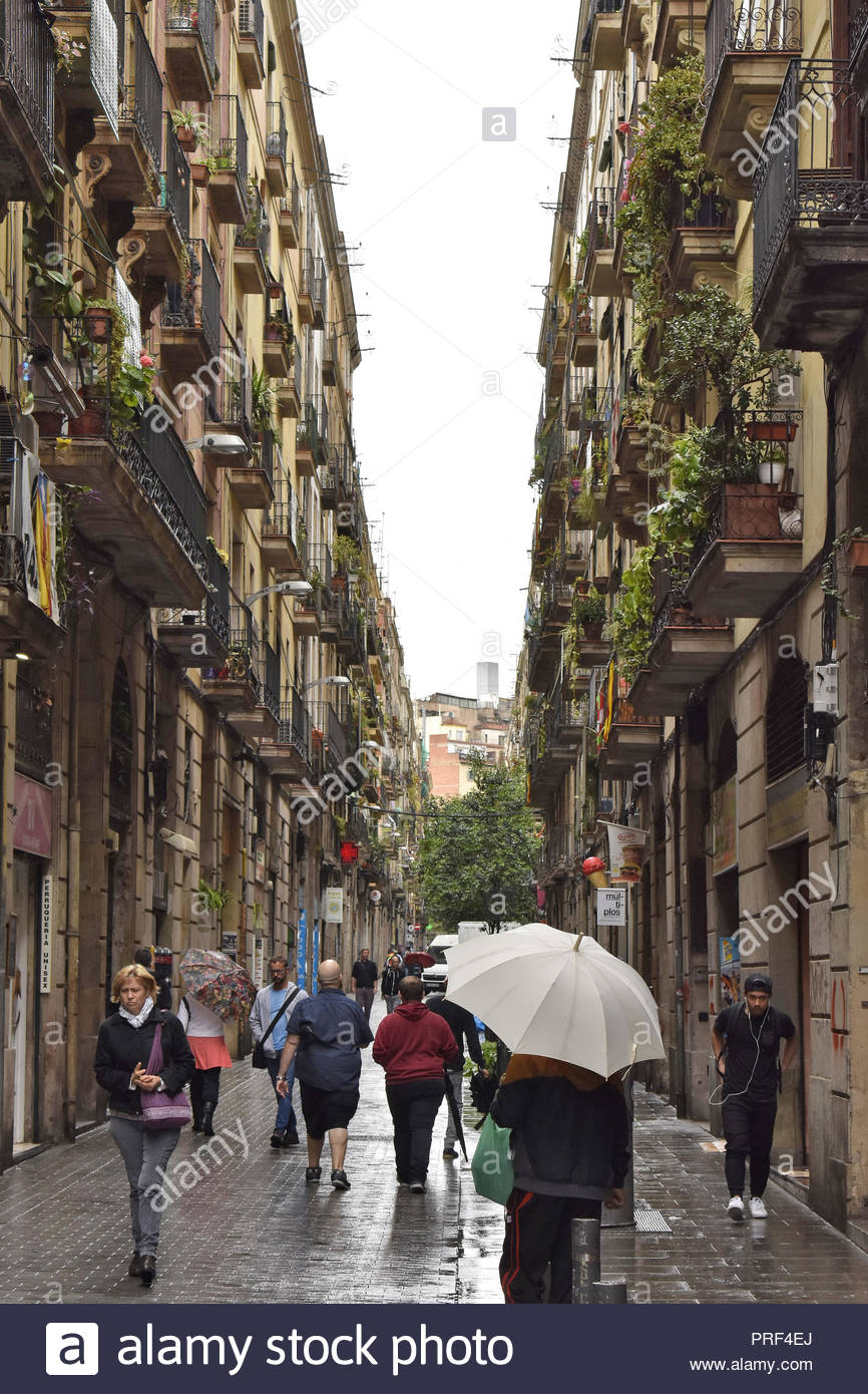 Street with residential properties, people walking through El Raval district on rainy day, Ciutat Vella Barcelona Spain Europe. - Stock Image