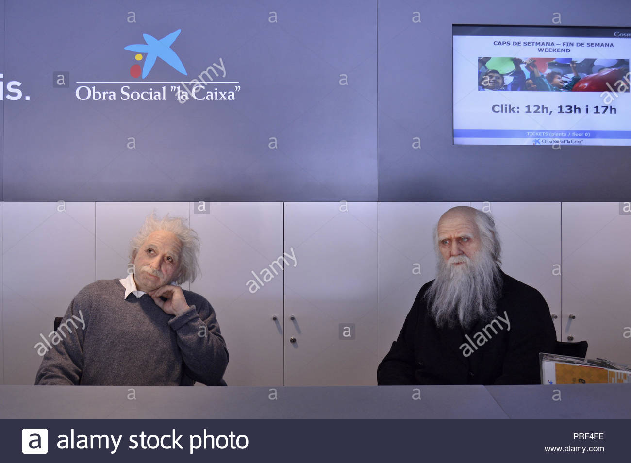 Wax figures of Albert Einstein and Charles Darwin, famous scientists, installed at reception desk in CosmoCaixa science museum, Barcelona Spain. - Stock Image