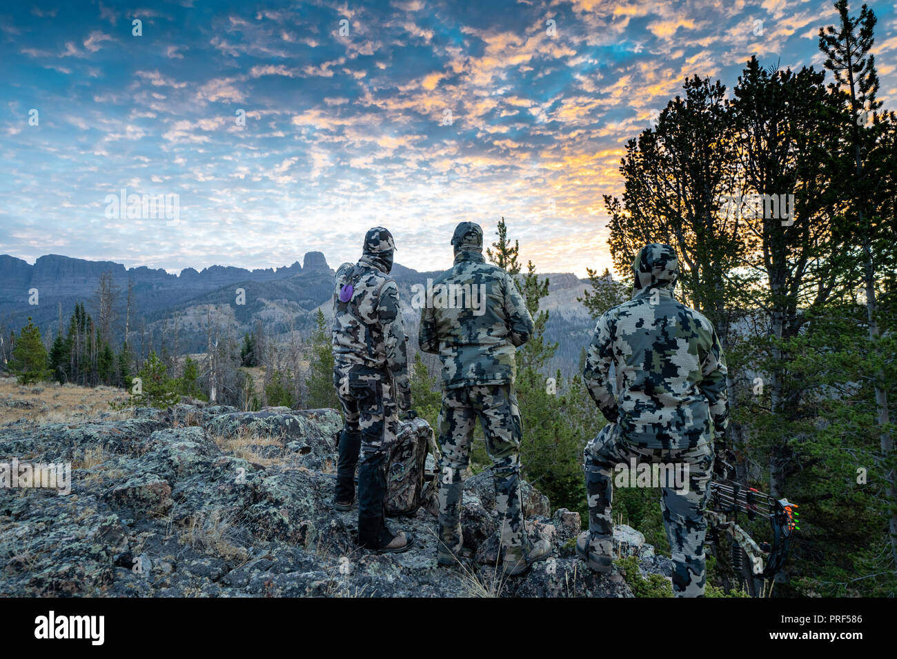 Three adult male hunter friends, unrecognizable,  stand on a mountain ridge looking for elk to hunt during bow archery season. Wearing camouflage - Stock Image