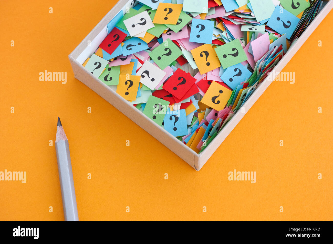 Pencil and question marks in a paper box on yellow background. Concept image. Close up. Stock Photo