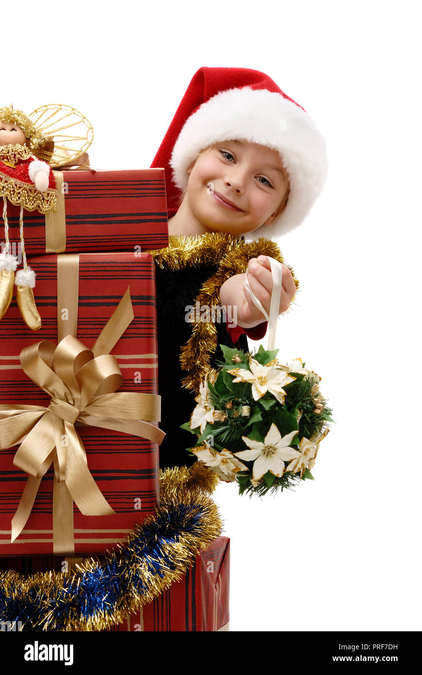 Cute little girl in a Santa Claus cap with Christmas gifts on a ...