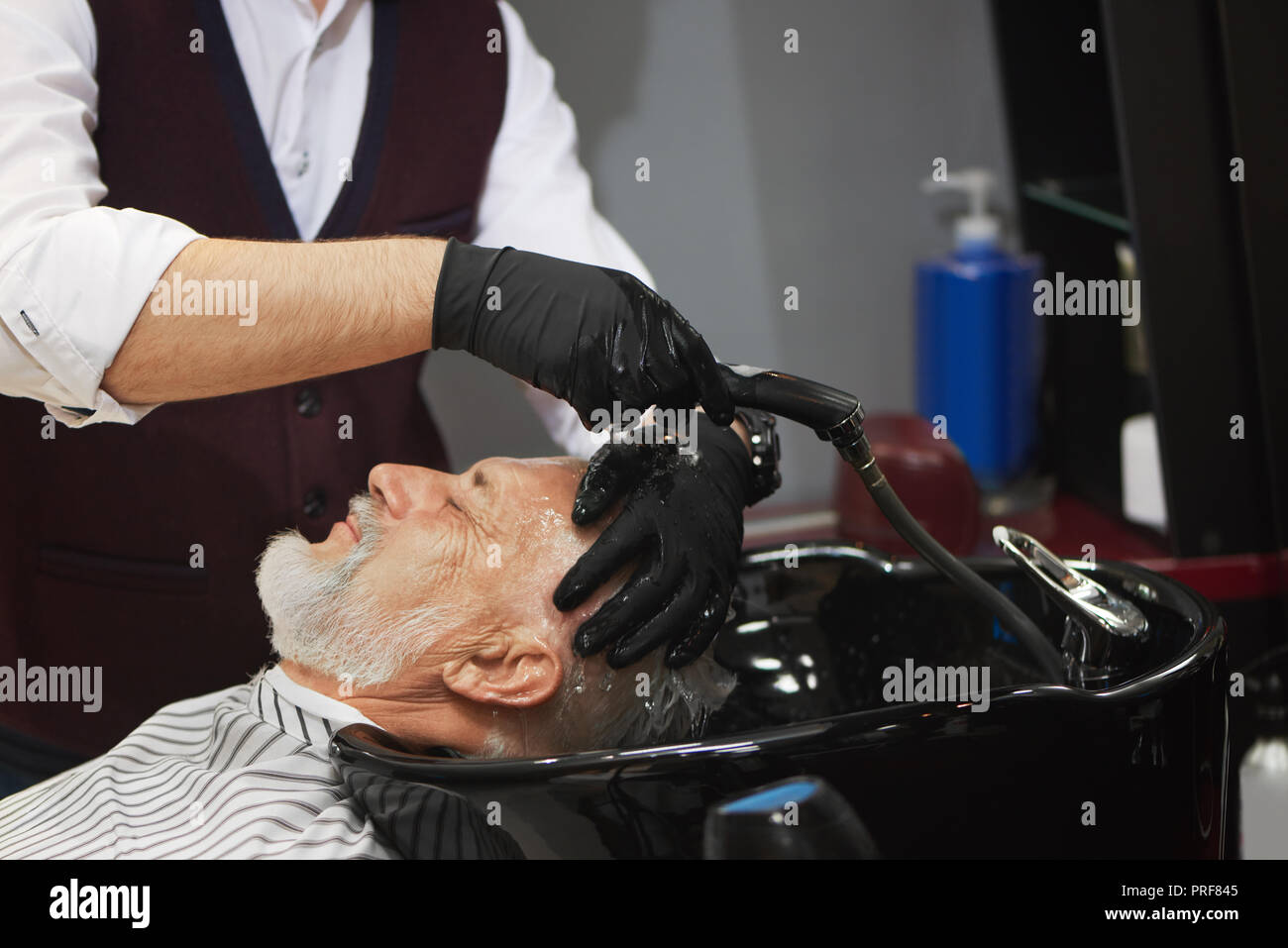 Side view of old man with grey hair holding head in black wash basin. Unrecognizable barber in black gloves washing head of his client. Concept of barbershop procedures. - Stock Image