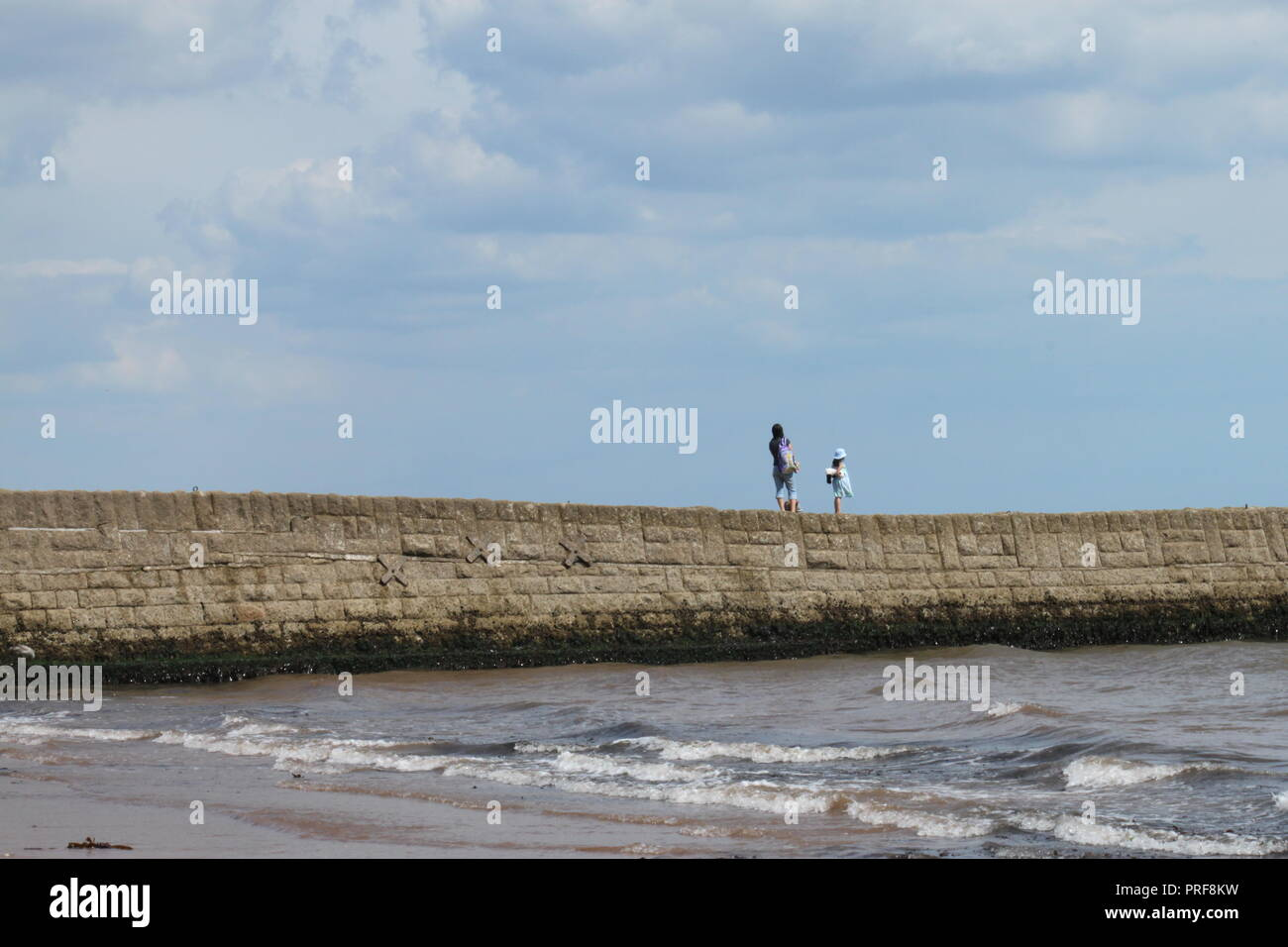 woman and girl standing on a pier at Dawlish, Devon. - Stock Image