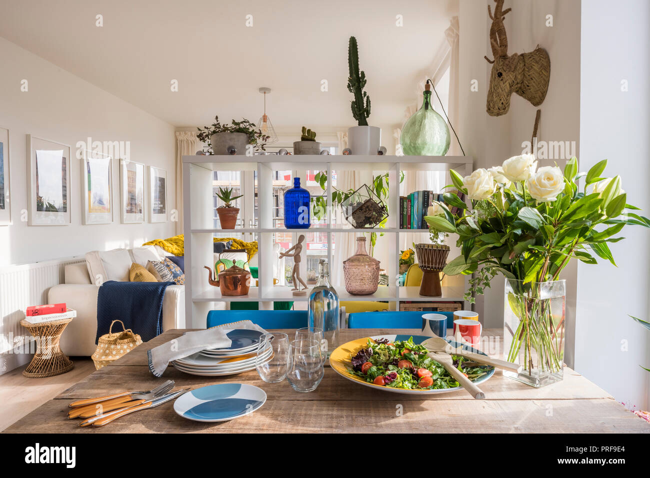 Salad on scaffold board dining table with shelf unit room divider - Stock Image