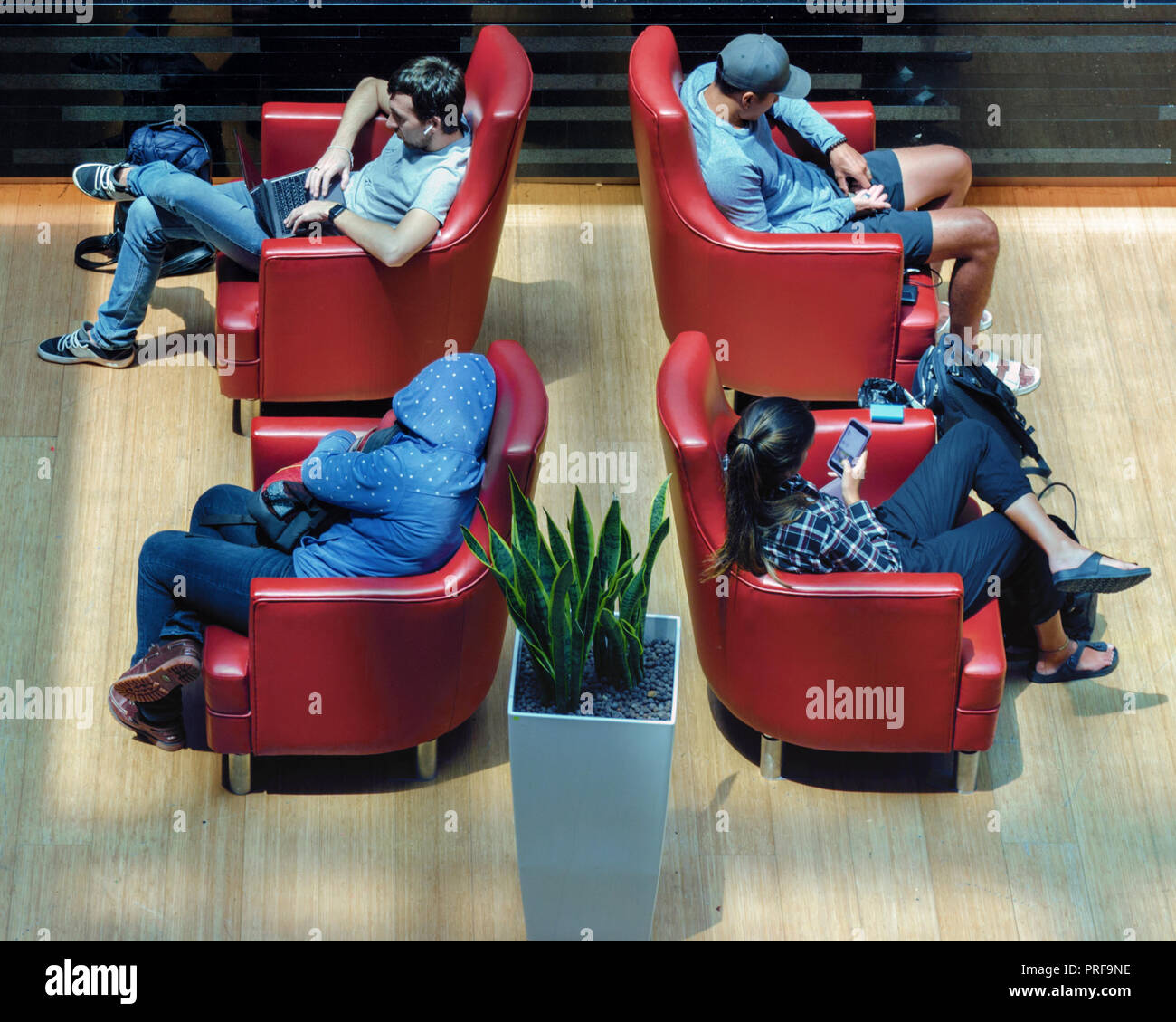 Top view of separate people, everyone does not pay attention to each other. Isolation, alienation, Introvert. Airport waiting room with armchairs. - Stock Image