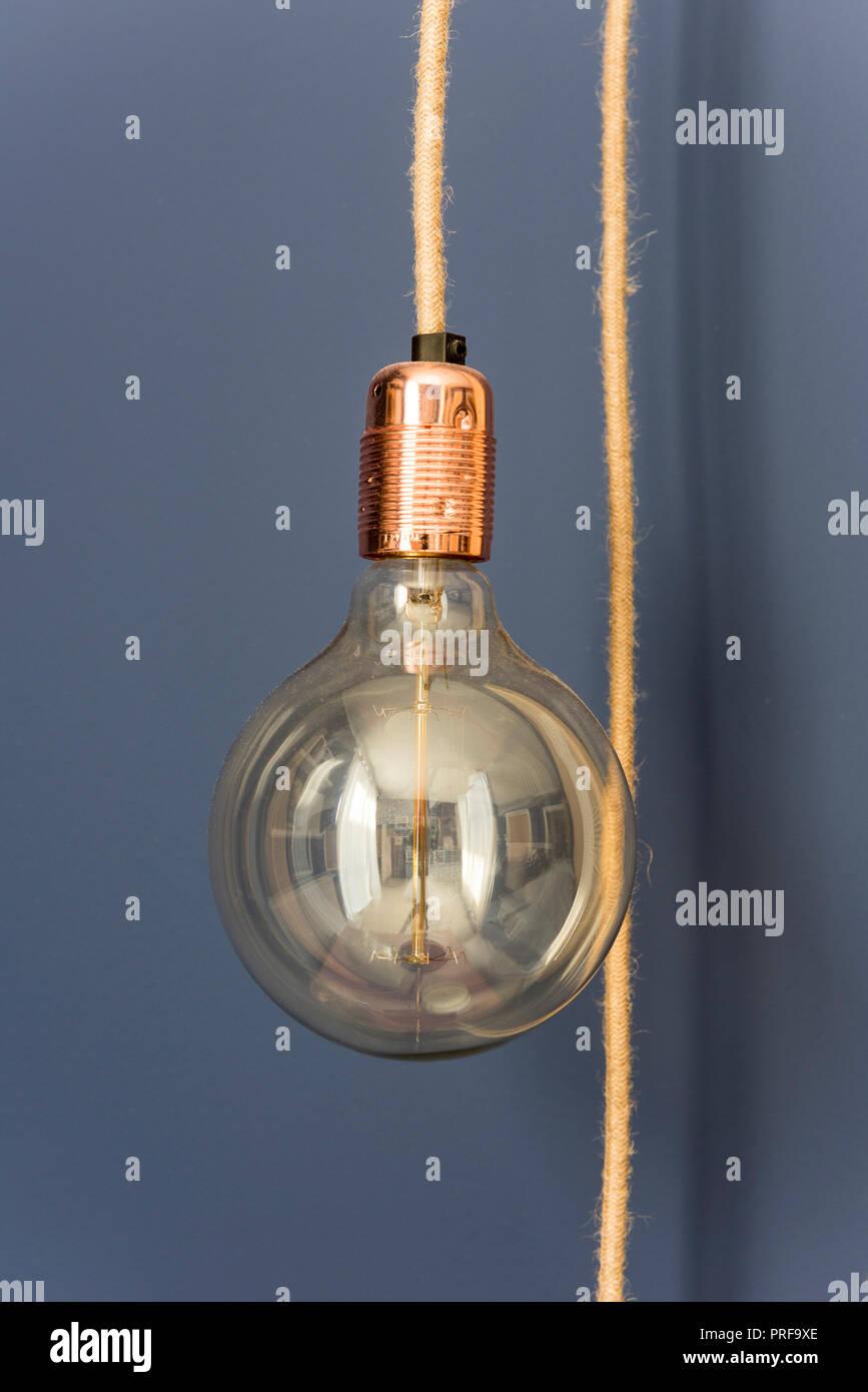 Single filament lightbulb hanging on cord - Stock Image