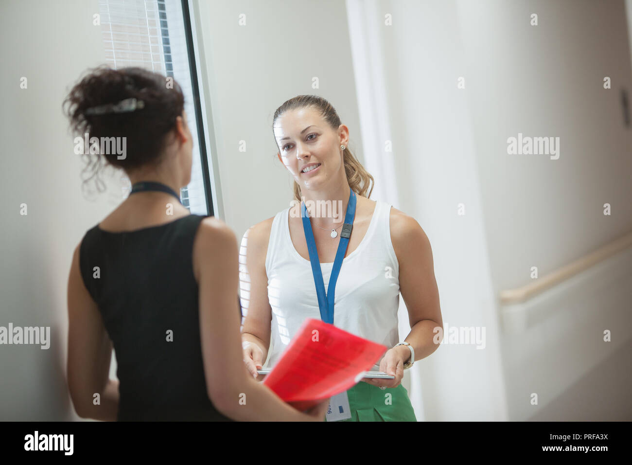 Young ladies in working mode chatting in corridor - Stock Image