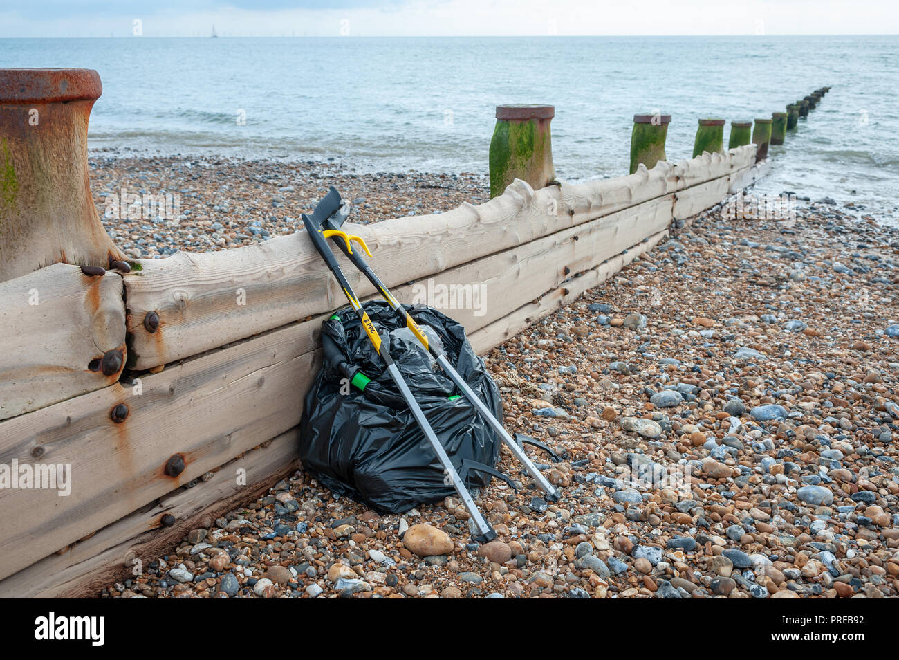 Beach clean up. A black bag full of rubbish collected from the beach and two litter pick up tools leaning on a wooden groyne on the beach. - Stock Image