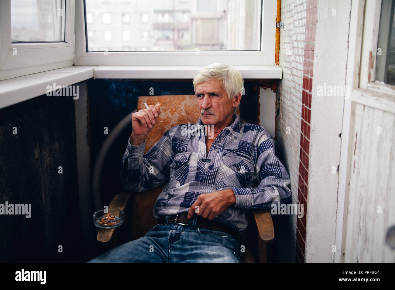 portrait of a gray-haired man 60 years old. A man sits in a chair and smokes a cigarette - Stock Image