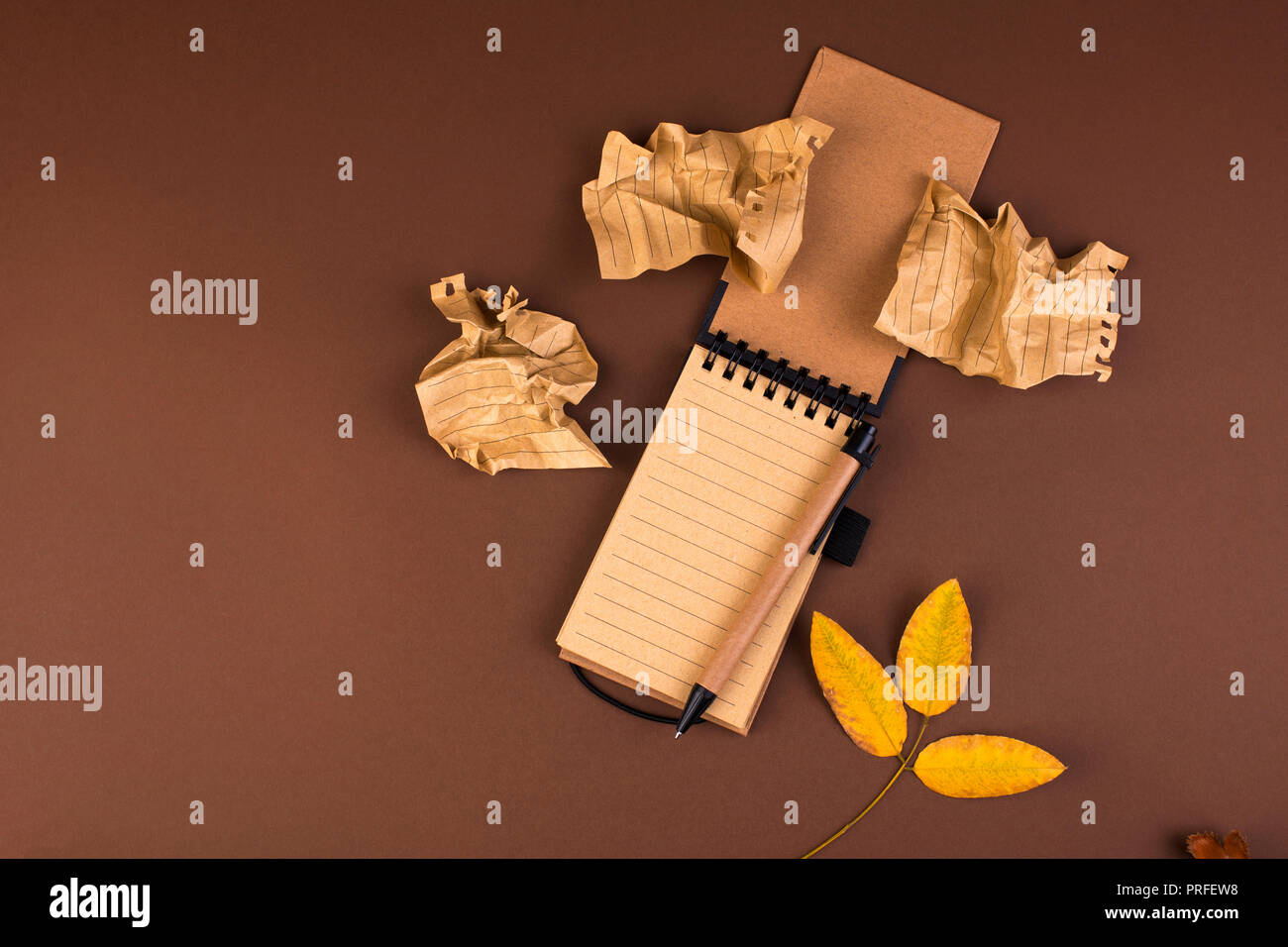 An open notebook for records and crumpled sheets on a brown background. Office planning. Free space for text. Autumn atmosphere and yellow leaves. Top - Stock Image