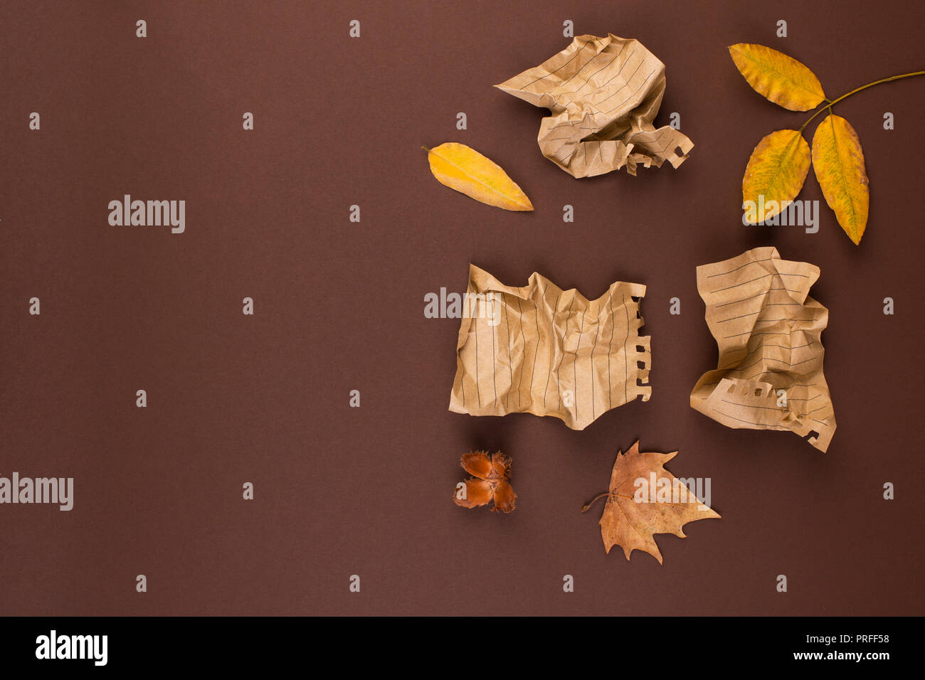 Notepad and crumpled sheets for writing, difficult work to write a letter. Free space for text. Autumn atmosphere and yellow leaves. Top view. Copy sp - Stock Image