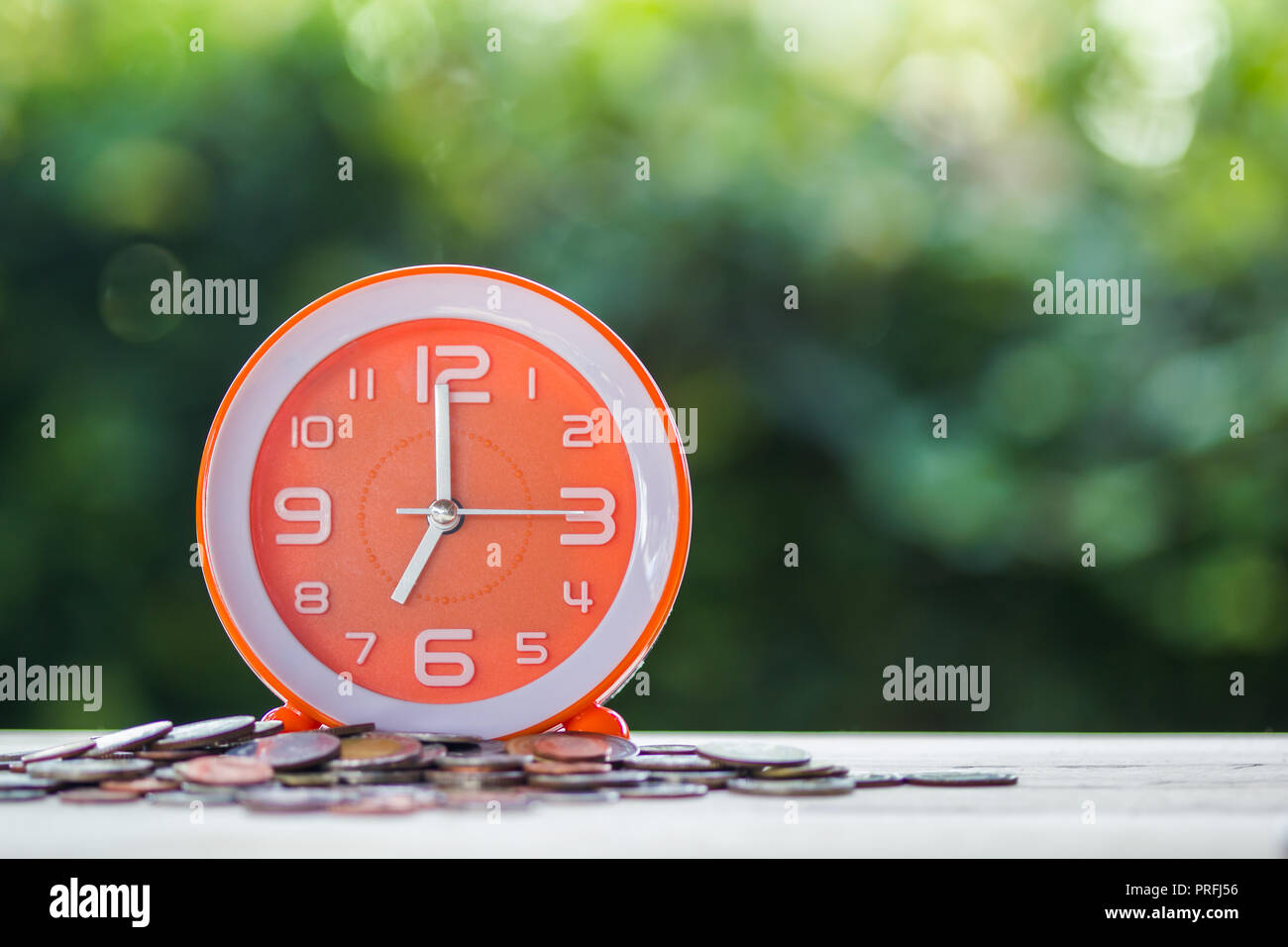 Time and money investment, Deadline loan money concept : Time on coins on table with green bokeh as background. Business finance with time and investm - Stock Image