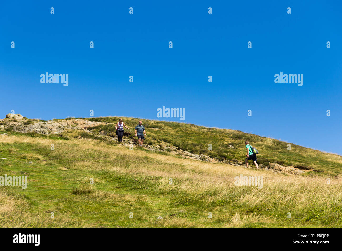 Three walkers approach each other on the footpath leading south from the summit of  Cat Bells (451 metres) near Keswick, Cumbria. Stock Photo