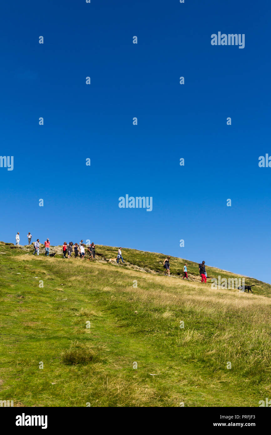 A group of young people and other walkers and their dogs on the footpath leading south from the summit of Cat Bells (451 metres) near Keswick, Cumbria Stock Photo