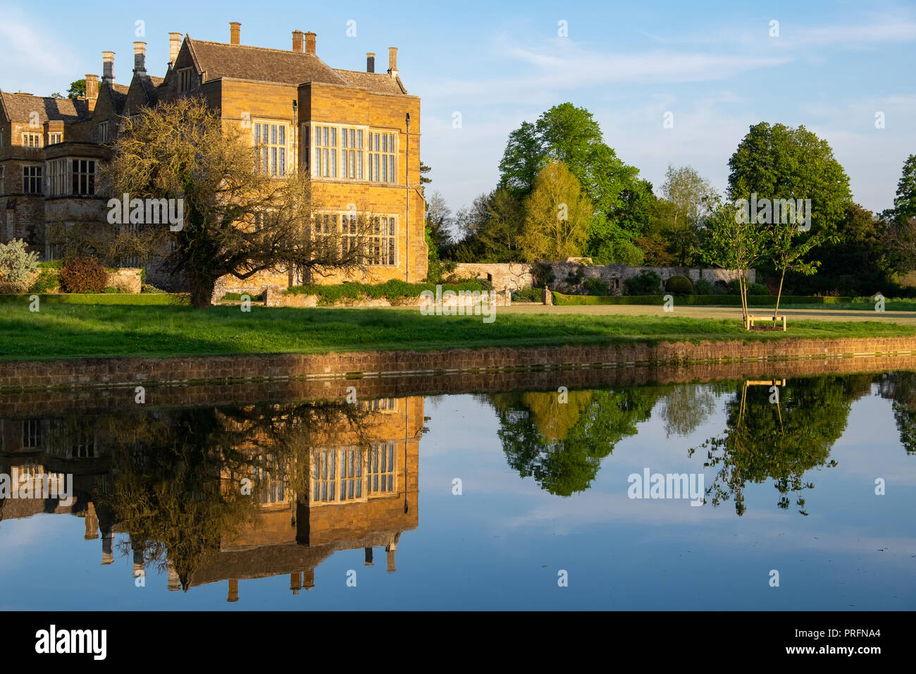 Broughton Castle, near Banbury, home of the Fiennes family in golden evening light with reflections in the still water of the moat. Open to the public Stock Photo