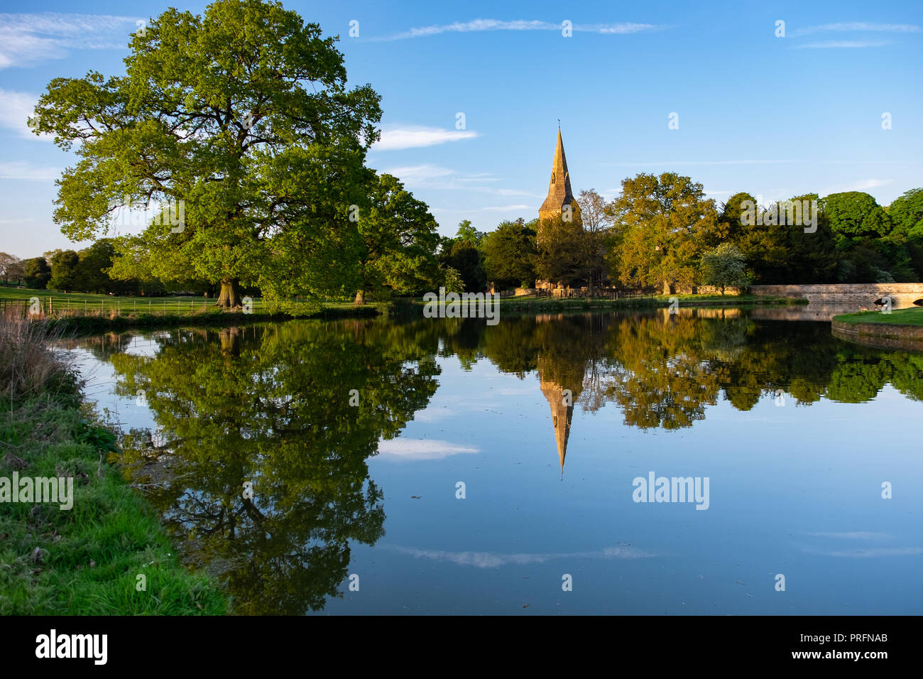 Broughton Castle and church, near Banbury, home of the Fiennes family in golden evening light with reflections in the still water of the moat. Stock Photo